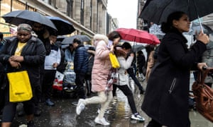 Shoppers jump over puddles of water as they hunt for bargains during the Boxing Day sales in central London.