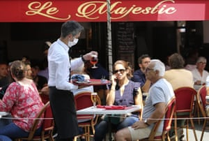 A bartender brings drinks to customers at a cafe in Saint Jean de Luz in south-west France