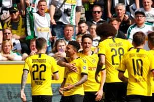 Borussia Dortmund's Jadon Sancho celebrates scoring their first goal with Christian Pulisic and teammates.