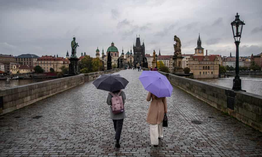 Women covered by umbrellas walk on an almost abandoned Charles Bridge in Prague, Czech Republic