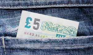 Close-up of a five pound note in a back pocket