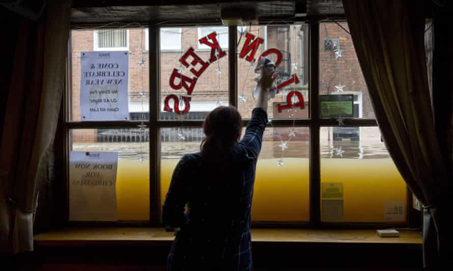 A woman cleans the inside window of her wine bar, as the floodwaters rise from the rivers Foss and Ouse, after they burst their banks in York.