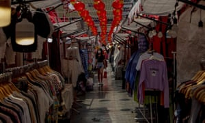 A shopper wearing a mask walks through an almost-empty street market aimed at Chinese tourists in Bangkok, Thailand, on 29 January.