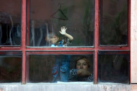 A Uighur woman look out from the window of an apartment Urumqi, China.