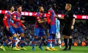 Cheikhou Kouyate of Crystal Palace (second on the right), Cenk Tosun (center) and teammates protest with referee Graham Scott.