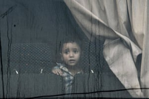 Athens, Greece: A boy sits in a bus during a police operation to evict migrants from the centre