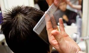 Teenage boy having his hair cut at a barbers in England
