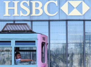 A man looks out from the top deck of a tram as he passes the local HSBC headquarters building in Hong Kong on October 29, 2018.