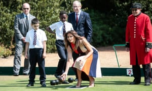 Melania Trump tries her hand at lawn bowls as Philip May watches during a visit to The Royal Hospital Chelsea