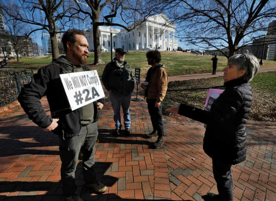 A gun rights activist, left, discusses the issue with a gun control proponent outside the Virginia state capitol building.