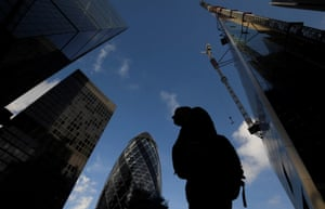 A worker walks past office skyscrapers in the City of London financial district