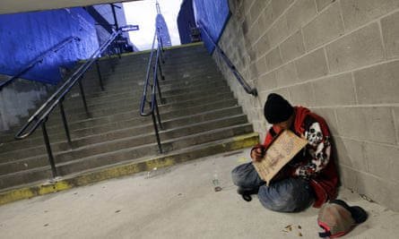 A homeless man holds a sign asking for money while sitting in the entrance to a subway station in New York, New York.