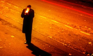 Shadowy man lights cigarette on dark street