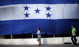 A woman and  man walk past a giant Honduran flag.
