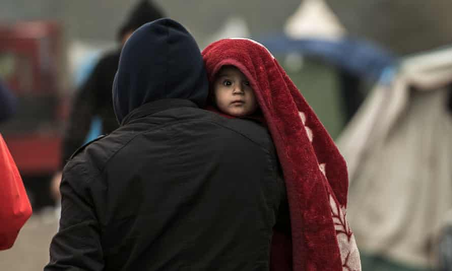 A migrant carries a child in a camp near Dunkirk