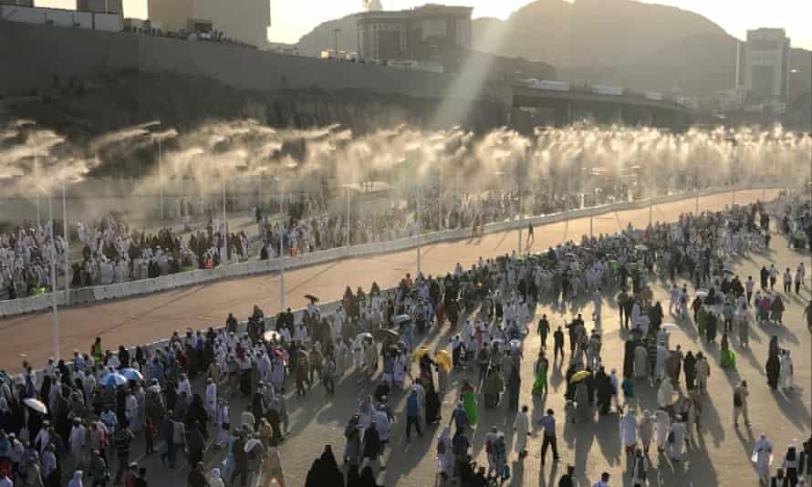 Pilgrims taking part in the Hajj in Mecca walk down a road with a water spray cooling system, part of an increasingly sophisticated support system required to beat the heat.