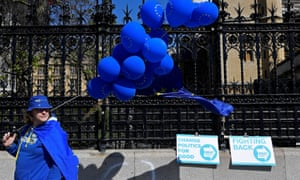An anti-Brexit protester stands next to Brexit party campaign placards outside of the Houses of Parliament