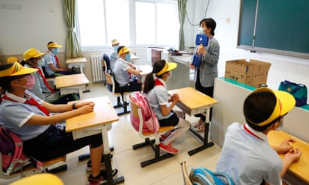A teacher distributes epidemic prevention materials for students at Fengtai No 1 Primary School in Beijing