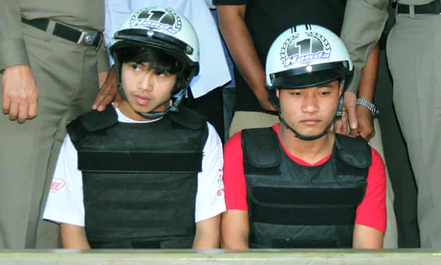 Burmese migrant workers Wai Phyo (eft) and Zaw Lin (right), attend a press conference with police on the beach of Koh Tao Island in 2014