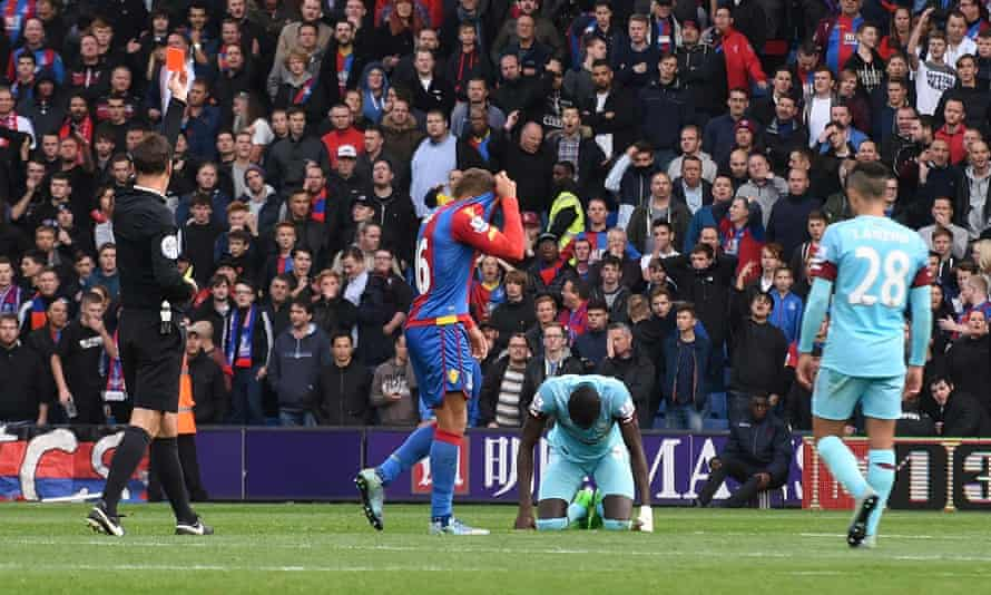 Dwight Gayle hides his head as he is sent off by Mark Clattenburg.