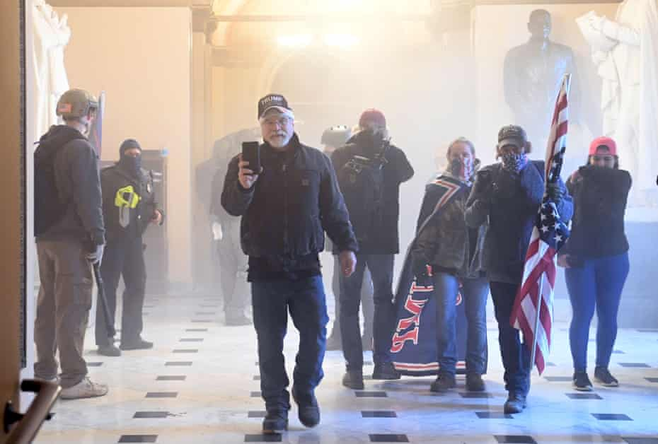Supporters of Donald Trump enter the US Capitol as teargas fills the corridor.
