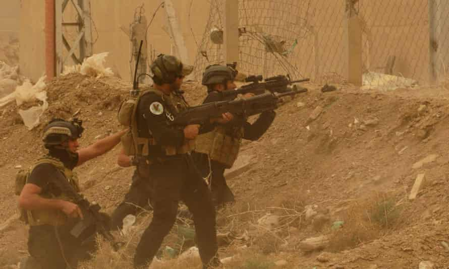 Security forces defend their headquarters against attacks by Islamic State extremists during a sandstorm in the eastern part of Ramadi.