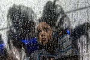 A Central American girl, travelling in the migrants' caravan, rides a bus outside a temporary shelter in eastern Tijuana.