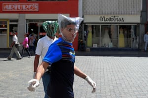 Men cover their faces with plastic bags in an attempt to protect themselves from the Covid-19 virus in Caracas, Venezuela