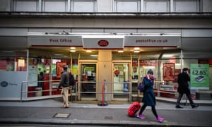 People walk past a Post Office branch in London
