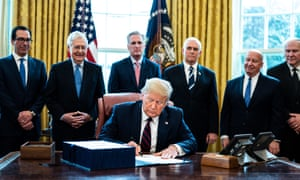 Trump participates in a signing ceremony for the coronavirus stimulus package in the Oval Office at the White House in Washington DC, on 27 March.