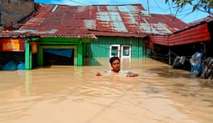 Tebing Tinggi, Indonesia: A man leaves his flooded home after thousands of houses were inundated by torrential rains in North Sumatra