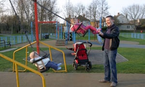 A man with his children in a playground. Hundreds are being closed by local authorities across England.