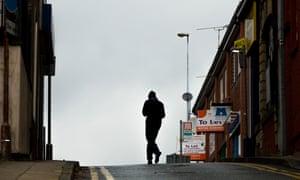 A man walks past a pawnbroker's shop in Rochdale town centre