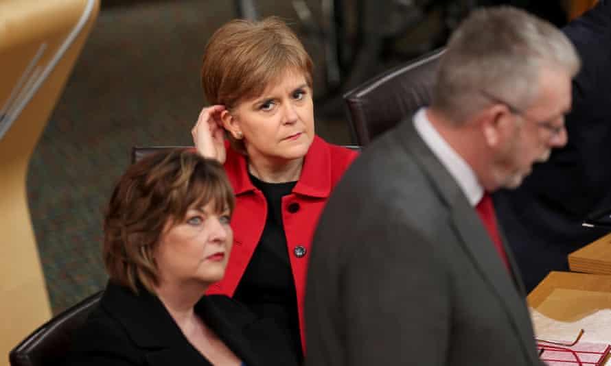 Nicola Sturgeon listens as MSP Mike Russell speaks during a Scottish parliament debate