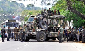 Sri Lanka's army soldiers stand guard a road after clashes.