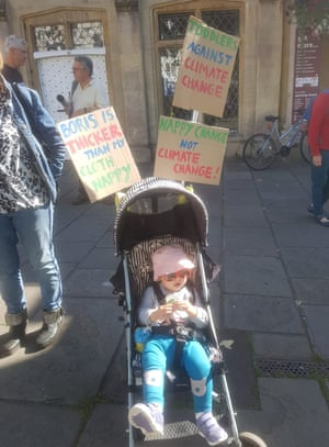 toddler sitting in a pram wearing a hat and sunglasses with handmade signs attached to the back of the pram saying nappy change not climate change, for example