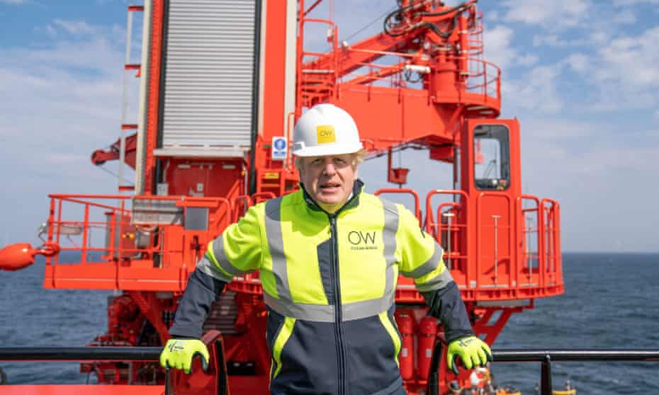 Man looking uncomfortable in hard hat and hi vis clothing, in front of some bright orange machinery and a calm sea