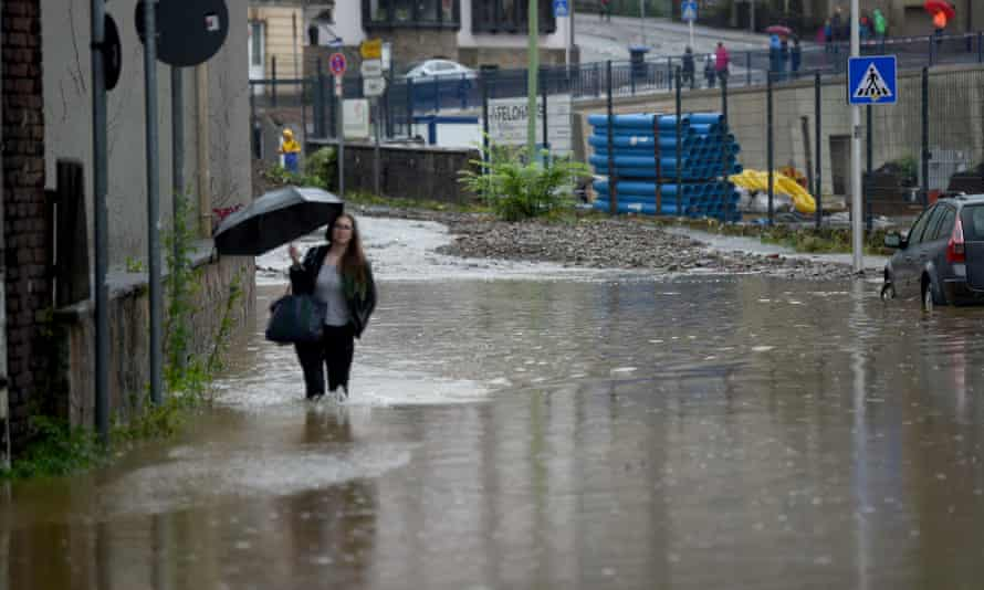 a woman with an umbrella walks along A flooded street in Hagen on 14 July.