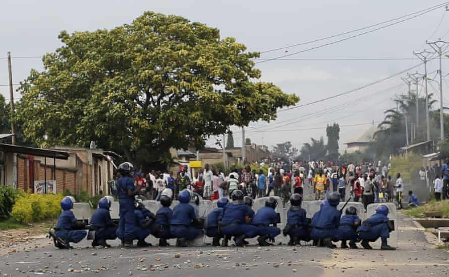 Burundi riot police face stone throwing demonstrators during clashes in the Musaga district of Bujumbura, Burundi, Tuesday April 28, 2015. Anti-government street demonstrations continued for a third day after six people died in protests against the move by President Pierre Nkurunziza to seek a third term.
