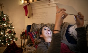 Happy young woman using digital tablet in Christmas living room