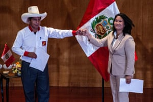 Peruvian rival presidential candidates Pedro Castillo (left), of the Perú Libre party, and Keiko Fujimori, of the Fuerza Popular party, bump fists at the signing of a pledge to democracy
