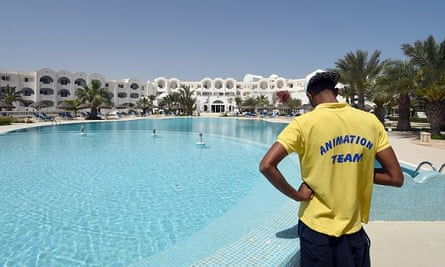 A lifeguard stands by an empty swimming pool.