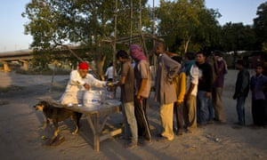 Poor men wait in a queue to receive food handed out in New Delhi. A universal basic income is being considered in India to tackle mass poverty.