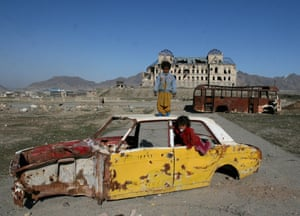 Kabul, 2007 children play in a destroyed car in front of the former Afghan King Darul Aman's palace