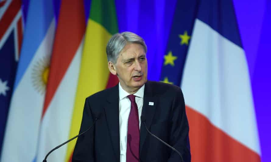 Philip Hammond standing in front of a bunch of flags