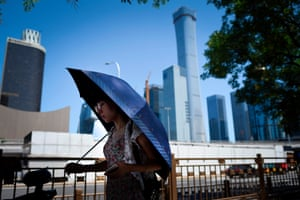 Beijing, China: A pedestrian tries to take shade in the city's business district