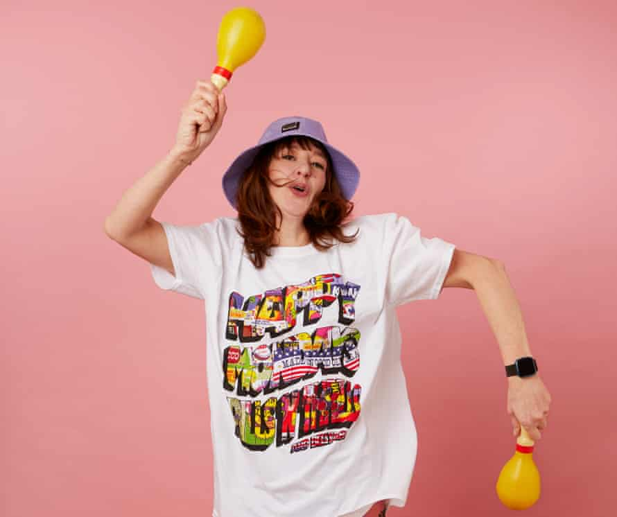 Zoe Williams shaking maracas against a pink background