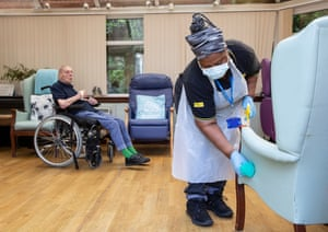 Eric Johnston, 93, at Eskgreen care home as cleaner Gladys disinfects seats.