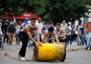 Demonstrators build a barricade with barrels
