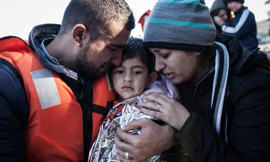 A boy is comforted by his parents after landing on Lesbos, Greece on Thursday.